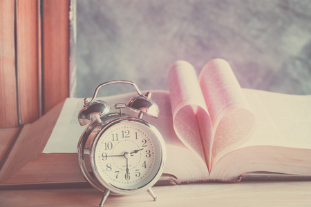 love shape: Heart book page with alarm clock in vintage effect style Stock Photo