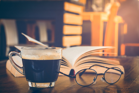 law school: A cup of black coffee with book and glasses on table in coffee shop