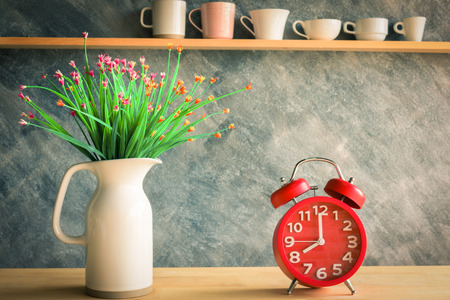Red alarm clock with flower in jug on table and various cups background Stock Photo - 71055685