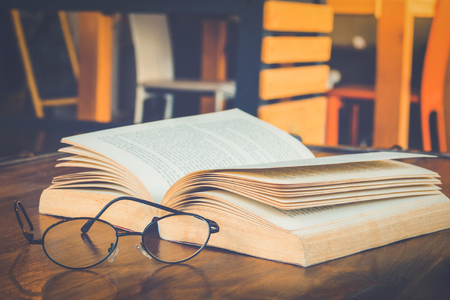 Book with glasses on table, vintage picture style