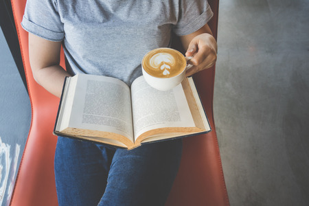 Soft photo of young girl reading a book and drinking coffee, top view