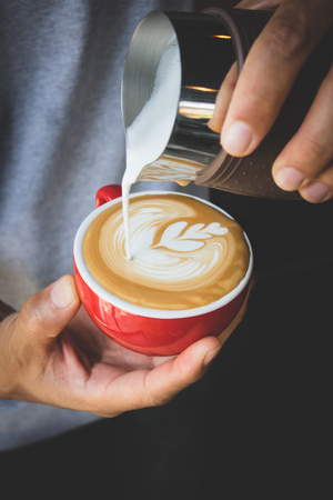 Vertical image of pouring milk to espresso coffee make latte art on red cup coffee Stock Photo