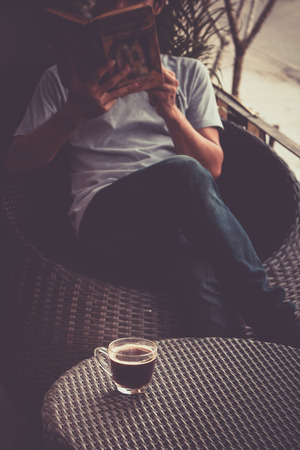 A man reading a book with drinking coffee