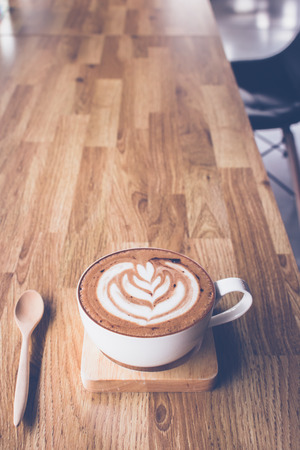 Coffee latte art on wooden table with leather seat in coffee shop