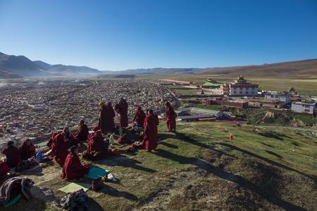 žák: Baiyu,China-October 17,2017; Monks praying ceremony on mountain at morning in Yarchen Gar monasterry a famous Lamasery in Baiyu, Sichuan, China