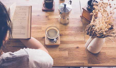 Young girl reading a book and drinking coffee, top view Stock Photo
