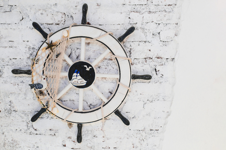 Old Ship Wheel (helm) on brick wall for decoration