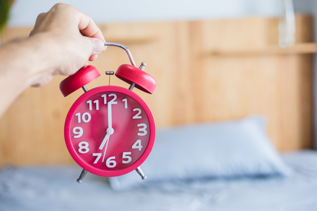 Hand holding red alarm clock with blurred bed background Stock Photo