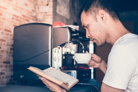 Handsome man drinking coffee and reading book at coffee shop Stock fotó