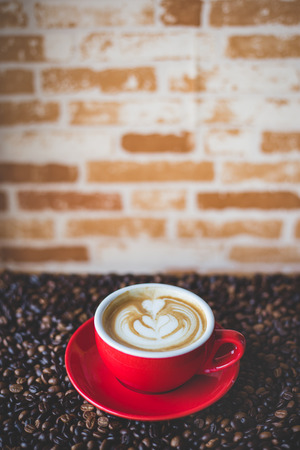 a red cup of coffee with coffee bean
