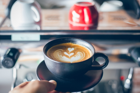 A cup of coffee  latte art  in black coffee with espresso machine background