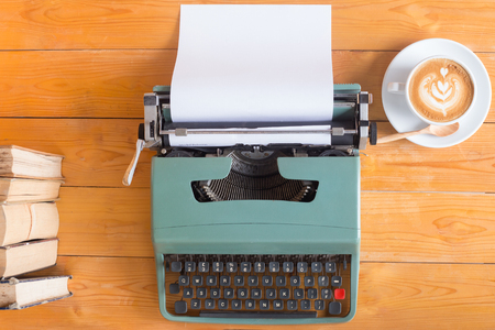 Old typewriter with a cup of coffee and books on wood table