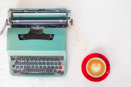Vintage typewriter with cafe latte coffee on white floor
