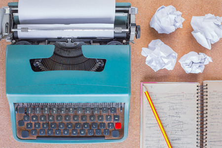 Typewriter on wooden desk background with papers ready for a new book or novel with many failed pages screwed up on desktop