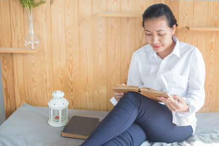 Soft image of young Asain woman reading book on her bed in bedroom Stock Photo