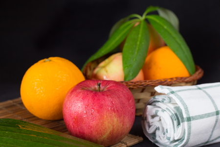 Apples with oranges on wood plate and wood basket in black space Stock Photo