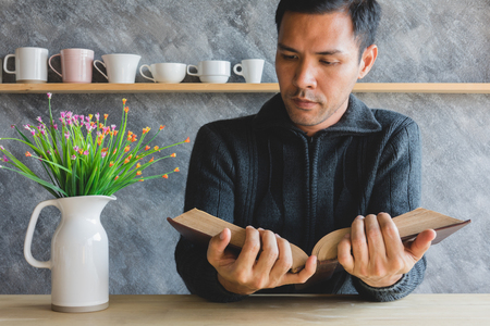 Asian man reading a book on table