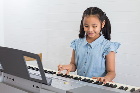 Asina children young girl playing piano in music room at school . 版權商用圖片