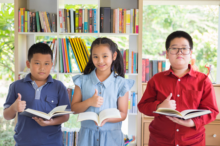 Asian boy and asian girl are standing in front of bookshelf and reading together with lif thumb up all Stok Fotoğraf