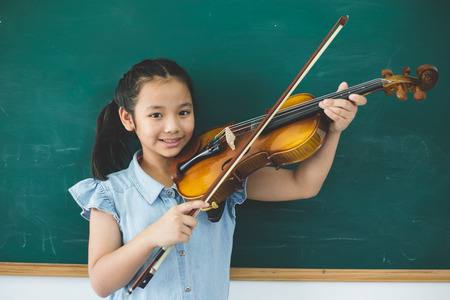 A littel cute girl playing violin on music class room at school Banque d'images