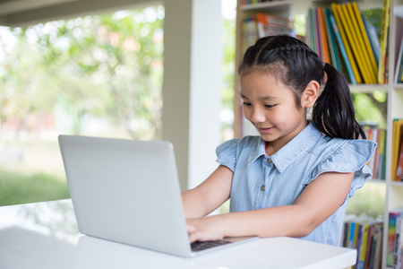 Young girl using computer at elementary school. Happy female child learning to use internet in a computer room. Stockfoto