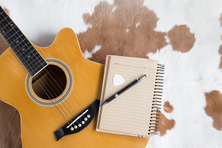 Classic acoustic guitar and and note with pen  for composing on leather background