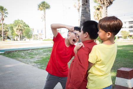 Młodzi studenci chłopcy walczą w parku