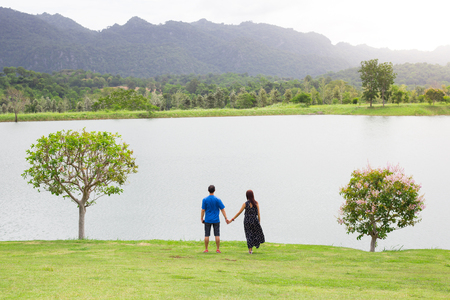 Behind of couple holding hand with full nature grass field , lake , mountain and tree . Romance seen Stock Photo