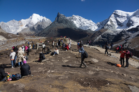 DAOCHENG, SICHUAN , CHINA - OCTOBER 23, 2018 : Unidentified tourists taking photos on walkway at Yading national reserve, Daocheng county, Sichuan province, China. Editorial