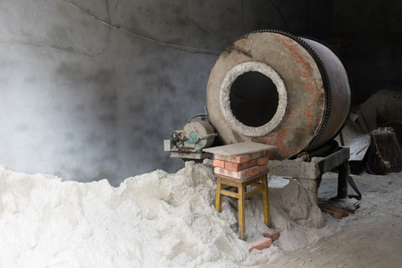 Cement mixer machine at construction site, tools and sand Stock Photo