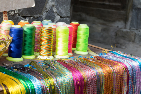 Spools of colorful silk thread on shelf Stock Photo