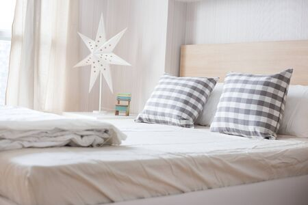 Luxury pillows on white bed in bedroom