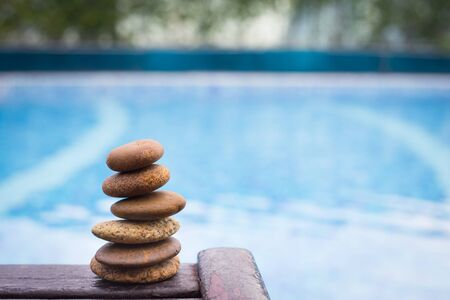 Zen stones on wooden banch on pool