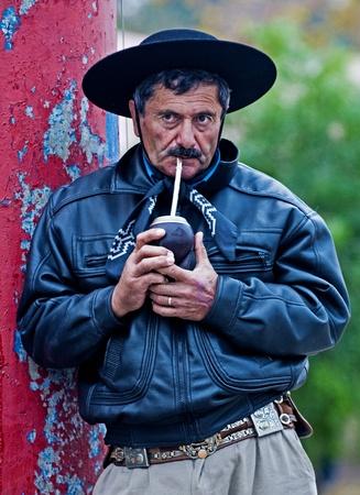 montevideo: MONTEVIDEO , URUGUAY  - APRIL 11 2009 : participant in  Gauchos show drink yerba tea