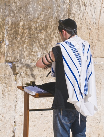 judaica: JERUSALEM , ISRAEL - AUG 06 2008 :  A jew lay tefillin in The western wall an Important Jewish religious site located in the Old City of Jerusalem