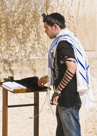 JERUSALEM , ISRAEL - AUG 06 2008 :  A jew lay tefillin in The western wall an Important Jewish religious site located in the Old City of Jerusalem