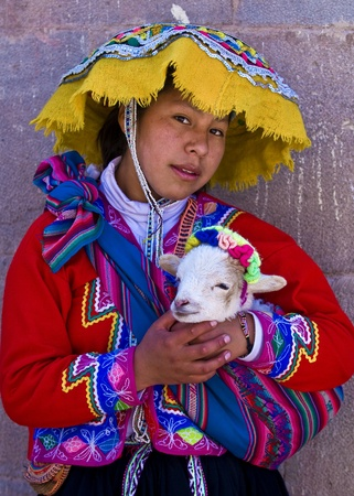 peruvian culture: CUSCO , PERU - MAY 27 : Unidentified Peruvian girl in traditional colorful clothes holding a lamb in here arms in the  Editorial