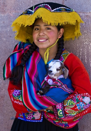 CUSCO , PERU - MAY 28 : Unidentified Peruvian girl in traditional colorful clothes holding a lamb in here arms in the