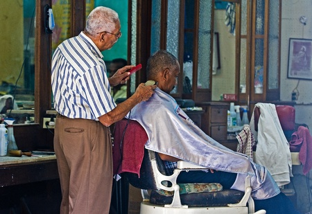 Caragenas de Indias , Colombia - December 21 2010 : Colombian man getting his hair cut in an old fashioned barber shop Stock Photo - 10605197