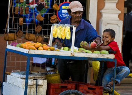 CARTAGENA DE INDIAS , COLOMBIA - DEC 21:Unidentified colombian man with his child, sell fruits in the street in Cartagena de Indias on December 21 2010