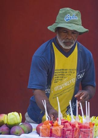 comida colombiana: CARTAGENA DE INDIAS, COLOMBIA - 21 de diciembre: el hombre no identificado colombiano vender frutas en la calle de Cartagena de Indias el 21 de diciembre 2010