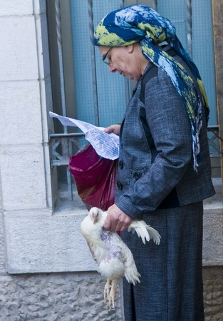 exprassion: JERUSALEM - OCT 06 : An ultra Orthodox Jewish woman hold a chicken and pray during  the Kapparot ceremony held in Jerusalem Israel on October 06 2011.