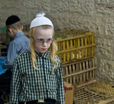 exprassion: JERUSALEM - OCT 06  : An ultra Orthodox Jewish boy near a cages with chickens use for the Kapparot ceremony held in Jerusalem Israel on October 06 2011