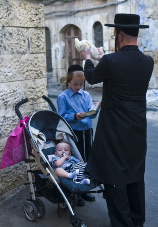 exprassion: JERUSALEM - OCT 06 : An ultra Orthodox Jewish man waves a chicken over his childrens heads during the Kaparot ceremony held in Jerusalem Israel in October 06 2011  Editorial