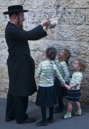 JERUSALEM - OCT 06 : An ultra Orthodox Jewish man waves a chicken over his childrens heads during the Kaparot ceremony held in Jerusalem Israel in October 06 2011  Editorial