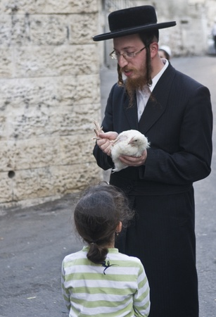 exprassion: JERUSALEM - OCT 06 : An ultra Orthodox Jewish man waves a chicken over his daughters head during the Kaparot ceremony held in Jerusalem Israel in October 06 2011  Editorial