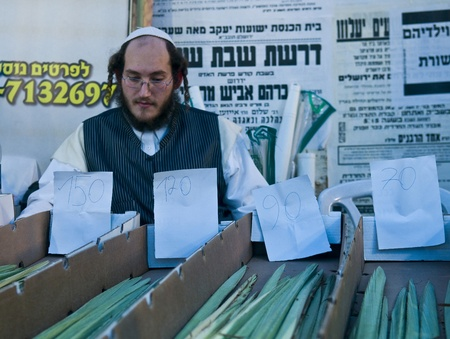 succot: JERUSALEM - OCTOBER 10 2011 : An ultra-orthodox Jewish man sells Lulav in the market Editorial