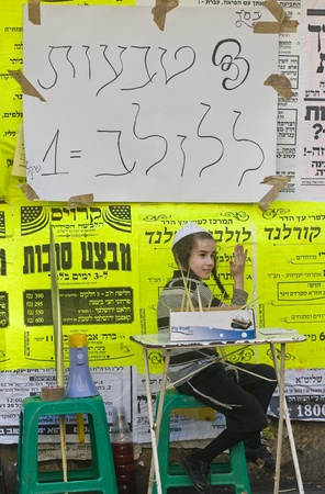 raligion: JERUSALEM - OCT 10 : An ultra-orthodox Jewish child sells Lulavs ring in the Four spesies market in Jerusalem Israel on October 10 2011 , Lulav is one of the Four spesies  used during the celebration of Sukot