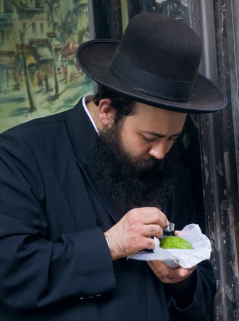 JERUSALEM - OCTOBER 10 2011 : An ultra-orthodox Jewish man inspects an Etrog Stock Photo - 10839128