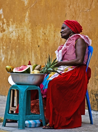 colombian food: CARTAGENA DE INDIAS , COLOMBIA - DEC 21:Unidentified Palenquera woman sell fruts in Cartagena de Indias on December 21 2010,Palenqueras are  a unique African descendat ethnic group found in the north region of South America